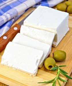 Feta cheese, knife, rosemary, olives, blue checkered napkin on the background of wooden boards
