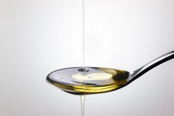 Olive oil pouring into spoon