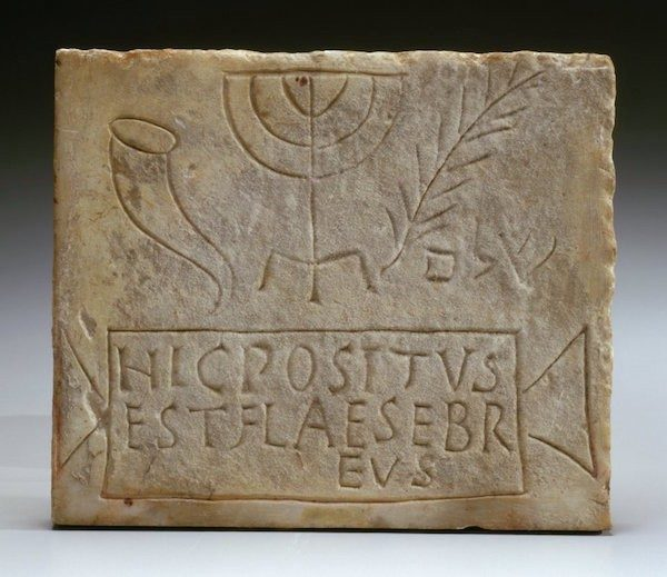 Jewish burial plaque from Italy depicting a shofar, menorah, palm, and text.