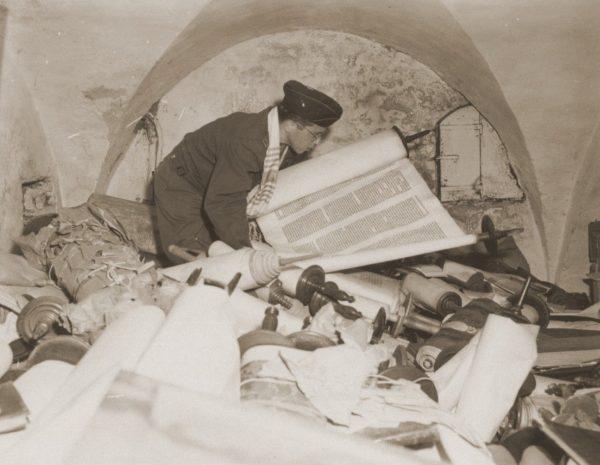Chaplain Samuel Blinder examining Torah scrolls.