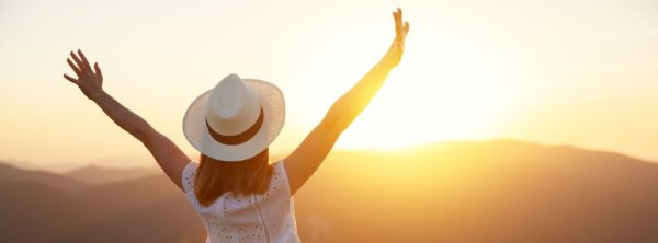 Woman with arms raised in front of sunset, representing happiness and plans for change in new year.