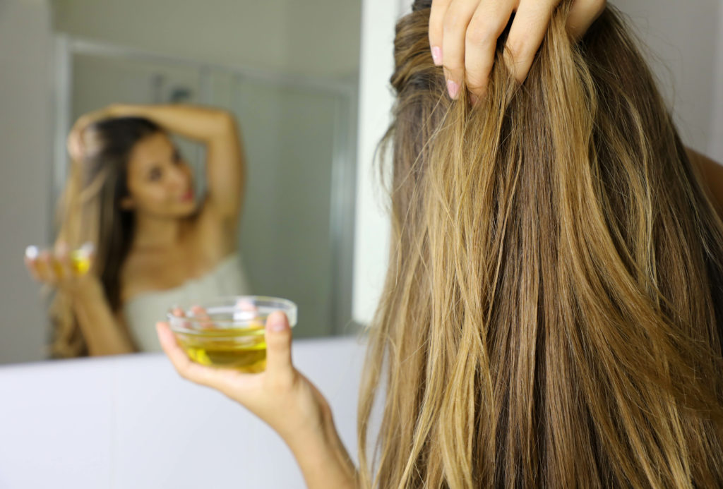 Young woman applying olive oil mask on hair in front of a mirror