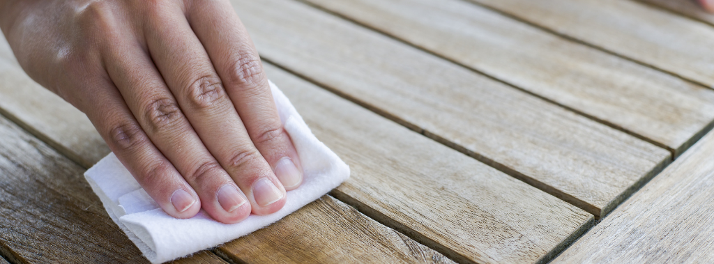 Hand wiping down a wooden table with cloth and olive oil, demonstrating a use of olive oil for household maintenance.
