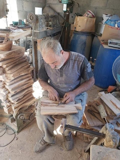 Qiesieh family members sit in their workshop, meticulously preparing their first order of olive wood cutting boards for My Olive Tree.