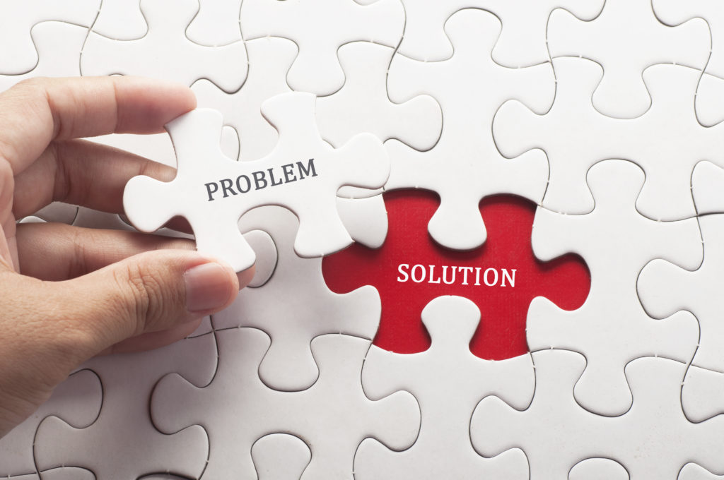 Hand holding a puzzle piece with the word problem on it over a space in the puzzle with the word solution.