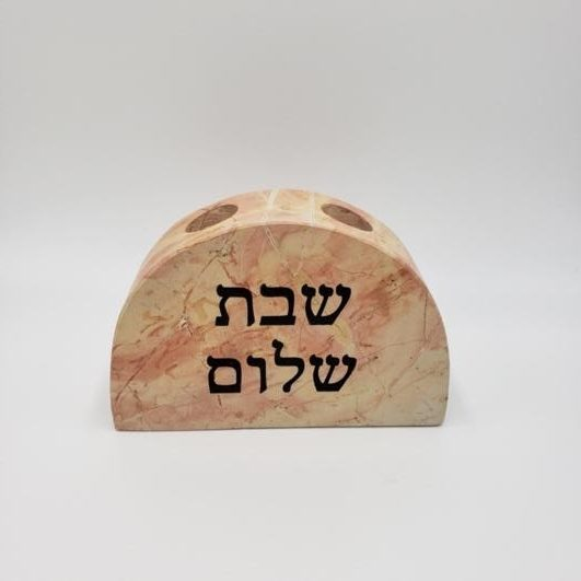 """A close up of the Jerusalem stone candle holder with Hebrew words """"Shabbat Shalom"""" etched on"""