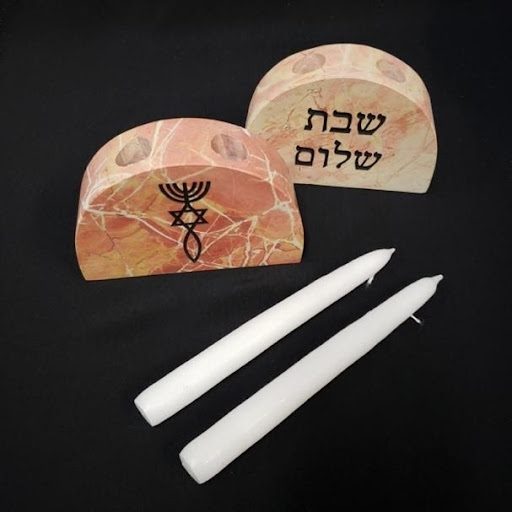 AN image of two candles and two Jerusalem stone candle holders